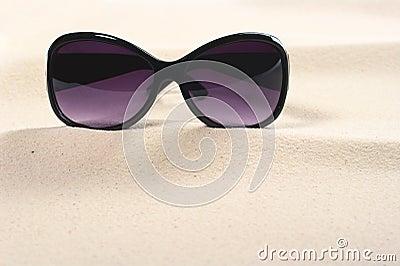 Óculos de sol na areia