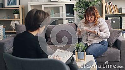 Överviktig ung dam som upp till öppnar den erfarna psykologen under konsultation arkivfilmer