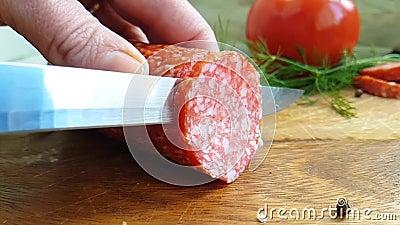 Übergeben Sie Hieb die Wurst mit Salami auf einem hölzernen, Tomate stock video footage