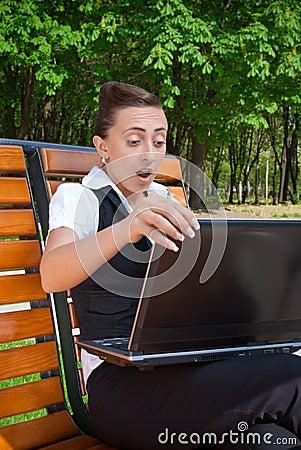 Überraschte junge Frau mit dem Laptop, der auf Bank sitzt