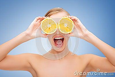 Überraschte junge Frau mit orange Scheiben