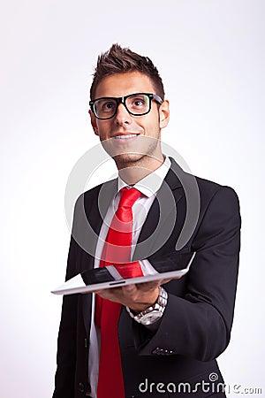 Überraschter junger Geschäftsmann, der eine Auflage anhält