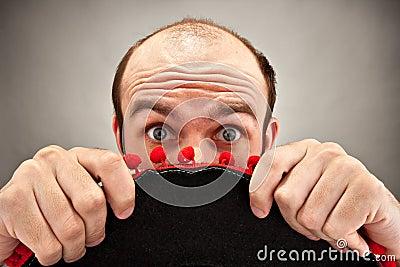 Überraschter Mann, der hinter Sombrerohut sich versteckt