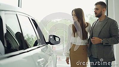 Überzeugter bärtiger Kerl der attraktiven jungen Paare und seine hübsche Freundin wählen das neue Automobil, das zusammen betrach stock video