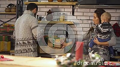 Ładna młoda kobieta z dzieckiem w ona ręki i brodaty mężczyzna w ciepłym pulowerze robi za prezent teraźniejszość pudełkach szcz? zbiory