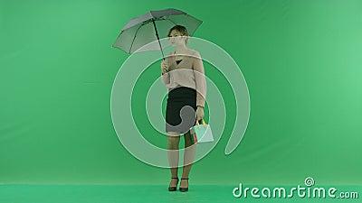 Ładna zakupy kobieta stoi z torba na zakupy i parasolem Żeński kupującego mienia torba na zakupy przód na zieleni zdjęcie wideo