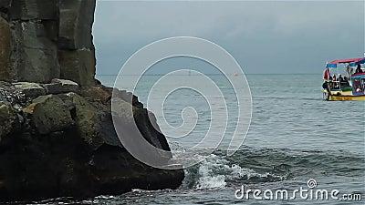 Łodzie unoszą się blisko zabytku, stoi w morzu zbiory