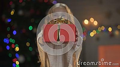 Śliczna blond dziewczyna pokazuje Bożenarodzeniowego prezent kamera, cudowna wakacyjna atmosfera zbiory