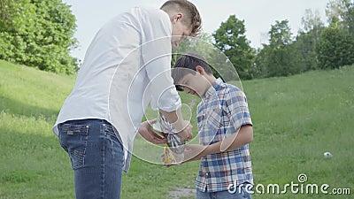 Śliczni potomstwa ojcują i jego uroczy syn patrzeje strzałki w pakunku w górę Śliczna chłopiec otrzymywał prezent od taty zdjęcie wideo