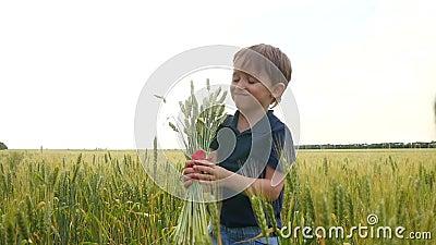 Śliczny chłopiec trzyma chleb pszenicy na polu i wdycha swój aromat rolnictwo zdjęcie wideo
