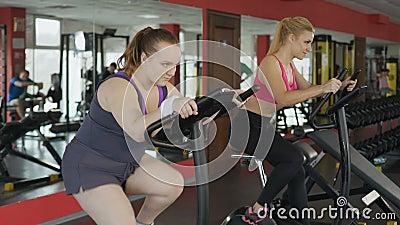 Śmieszny otyły damy jazdy post na stacjonarnym rowerze w sprawność fizyczna klubie, motywacja zbiory