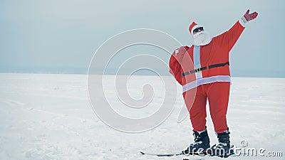Śnieżny teren z Mikołajem chodzącym na nartach i machającym rękami zbiory wideo