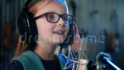 Śpiewanie dzieci w studio Mała dziewczynka śpiewająca piosenkę Widok z przodu — zbliżenie Dzieciak noszący słuchawki na zajęciach zbiory wideo