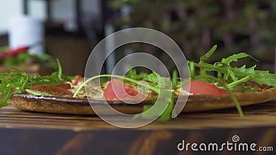 Świezi ziele spada na gorącym włoskim pizzy zwolnionym tempie Zamyka w górę pizzy z świeżymi ziele w pizzeria Karmowa podprawa