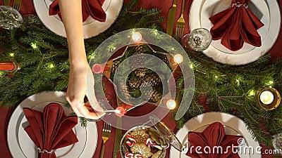 Żeńska ręka zaświeca boże narodzenie świeczki Świąteczny czerwień stołu położenie z girlandą zdjęcie wideo