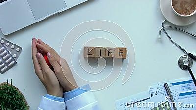 Życia słowo robić drewniani sześciany na stole, doktorskie ręki pokazuje zabawkarskiego kierowego odgórnego widok zbiory
