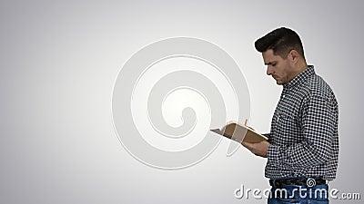 Άνδρας διευθυντής τυπικός ντυμένος κρατώντας σημειωματάριο περπατώντας και κάνοντας σημειώσεις κοιτώντας γύρω από το φόντο ντεγκρ απόθεμα βίντεο