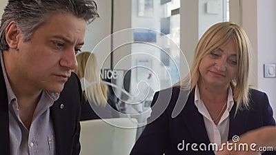 Άνδρας και γυναίκα που επιλέγουν το ταξίδι διακοπών στο ταξιδιωτικό γραφείο, κατάλογος κτυπήματος διευθυντών απόθεμα βίντεο