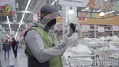 Άντρας με πράσινο γιοκ σε βιντεοκλήση με τη γυναίκα του βγάζει την προστατευτική του μάσκα και προσπαθεί να μάθει τι να αγοράσει  απόθεμα βίντεο