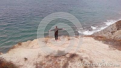 Άποψη Aero - μια όμορφη γυναίκα αισθάνεται ελευθερία στη φύση, να στέκεται πάνω από τη θάλασσα Χαρούμενο και υγιές κορίτσι αθλήτρ απόθεμα βίντεο