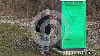 Άτομο που περιμένει κοντά στην πράσινη φορητή τουαλέτα στο πάρκο φιλμ μικρού μήκους