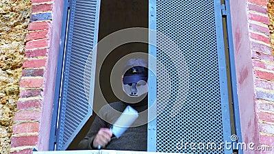 Άτομο στη μάσκα αποκριών με το μαχαίρι στο σπίτι στο ανοικτό παράθυρο απόθεμα βίντεο