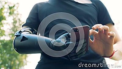 Άτομο του Yong με ένα τεχνητό χέρι που χρησιμοποιεί το smartphone Μελλοντική έννοια απόθεμα βίντεο