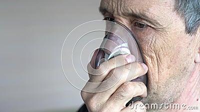 Ένας άντρας αναπνέει οξυγόνο χρησιμοποιώντας μάσκα Κοντινό πλάνο ενός γέρου που κάνει εισπνοή φιλμ μικρού μήκους