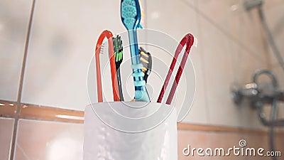 Ένας άντρας βάζει τις οδοντόβουρτσες του σε ένα στήριγμα πινέλου στο μπάνιο Κλείσιμο φιλμ μικρού μήκους