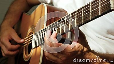 Ένας άντρας παίζει ακουστική κιθάρα Οι ακτίνες του ήλιου λάμπουν μέσα από τις χορδές μιας κιθάρας Μουσική και χόμπι φιλμ μικρού μήκους