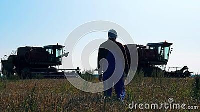 Ένας αγρότης περπατά σε ένα χωράφι με τρακτέρ φιλμ μικρού μήκους