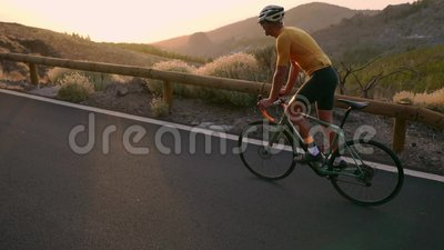 Ένας επαγγελματικός ποδηλάτης σε ένα κράνος και έναν αθλητικό εξοπλισμό οδηγά σε μια εθνική οδό βουνών στο ηλιοβασίλεμα σε σε αργ απόθεμα βίντεο