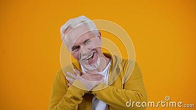 Ένας καλός γέρος που περνάει παλάμες στο στήθος, χαμογελώντας στην κάμερα, έννοια ειλικρίνειας απόθεμα βίντεο