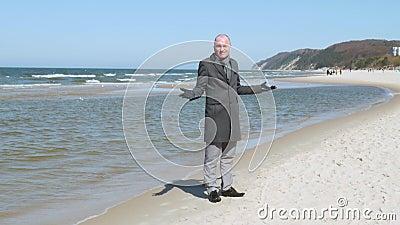 Ένας κομψός νεαρός άνδρας σε ένα παλτό στέκεται στην παραλία της θάλασσας, κοιτάζει γύρω και χαμογελά - χάνεται αυτός δεν ξέρει π φιλμ μικρού μήκους