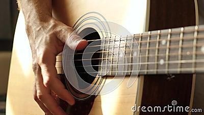 Ένας μουσικός βγάζει ήχο με τα δάχτυλά του από τις χορδές μιας κίτρινης ακουστικής κιθάρας, κοντινό πλάνο απόθεμα βίντεο