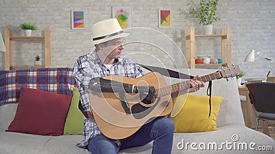 Ένας νεαρός άνδρας με καπέλο με βιονικό προσθετικό χέρι παίζει μια ηχητική κιθάρα που κάθεται σε έναν καναπέ απόθεμα βίντεο