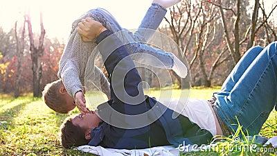 Ένας νεαρός πατέρας παίζει με ένα παιδί, κρατώντας το στην αγκαλιά του Οι ακτίνες του ήλιου διαπερνούν τα δέντρα Το γέλιο και η χ φιλμ μικρού μήκους