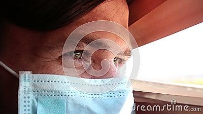 Ένας νεαρός όμορφος άντρας με μάσκα ιατρικού προσώπου κοιτάζει μέσα από τα περσινά παράθυρα φιλμ μικρού μήκους
