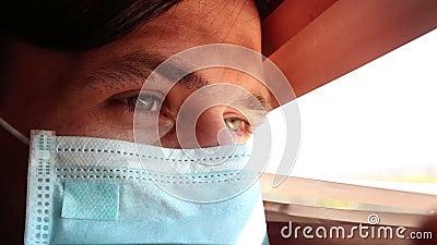Ένας νεαρός όμορφος άντρας με μάσκα ιατρικού προσώπου κοιτάζει μέσα από τα περσινά παράθυρα απόθεμα βίντεο