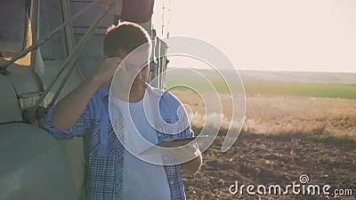 Ένας σκεπτικός αγρότης εργάζεται στον τομέα Χρησιμοποιεί μια ταμπλέτα, στέκεται κοντά στη γεωργική εφαρμοσμένη μηχανική απόθεμα βίντεο