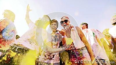 Ένας τύπος ρίχνει την κίτρινη σκόνη στον αέρα στο φεστιβάλ χρώματος holi σε σε αργή κίνηση