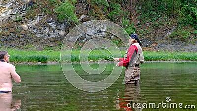 Ένας φωτογράφος με γυμνό κορμό και βαθιά μέσα στο νερό φωτογραφίζει έναν ψαρά κόκκινα ρούχα Αθλήματα και ψυχαγωγία σε στήριγμα φιλμ μικρού μήκους