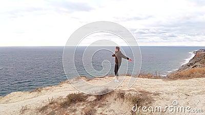 Ένας χαρούμενος και χαρούμενος αθλητής γυρίζει και νιώθει ελευθερία στην άκρη ενός γκρεμού Αθλητικός τρόπος ζωής φιλμ μικρού μήκους