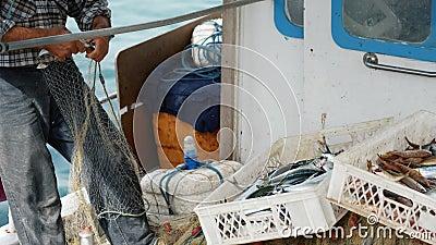 Ένας ψαράς βγάζει μια αλιεία από τα δίχτυα του ψαρέματος και ρίχνει στο καλάθι Ηλικιωμένος ναυτικός στο λιμένα Bodrum, Τουρκία απόθεμα βίντεο