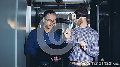 Ένα άτομο κινείται στα γυαλιά εικονικής πραγματικότητας κάτω από την καθοδήγηση του συναδέλφου του φιλμ μικρού μήκους
