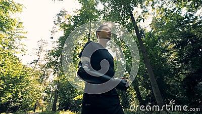 Ένα άτομο με έναν τεχνητό βραχίονα τρέχει κατά μήκος της αλέας Φουτουριστική ανθρώπινη έννοια cyborg απόθεμα βίντεο