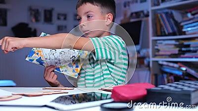 Ένα αγόρι κάθεται σε ένα τραπέζι και κάνει κίνηση για την εικόνα ενός παιδιού απόθεμα βίντεο