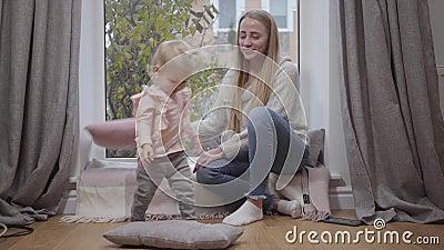 Ένα αρκετά καυκάσιο κοριτσάκι που παίζει με μαλακά μαξιλάρια και διασκεδάζει μαζί με μια νεαρή μητέρα Χαρούμενη γυναίκα που κάθετ απόθεμα βίντεο