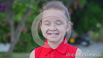 Ένα αστείο κοριτσάκι χαμογελά, κοιτώντας την κάμερα στο δρόμο, ένα χαριτωμένο παιδί παίζει στο δρόμο, κάνοντας ζωγραφιές με απόθεμα βίντεο