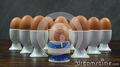 Ένα βραστό αυγό σε ένα κύπελλο αυγών με ρίγα με χαμογελαστό πρόσωπο μπροστά από μια ομάδα αυγών σε λευκά κύπελλα αυγών φιλμ μικρού μήκους